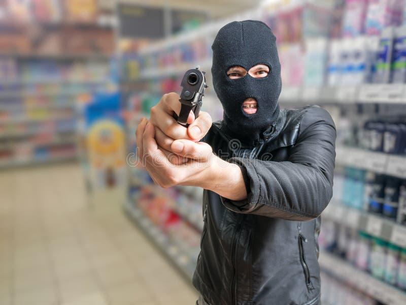 Furto in deposito Il ladro è tendente e minaccioso per la pistola in negozio fotografia stock