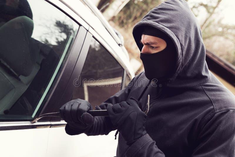 Furto di automobile - ladro che prova a rompersi nel veicolo fotografie stock