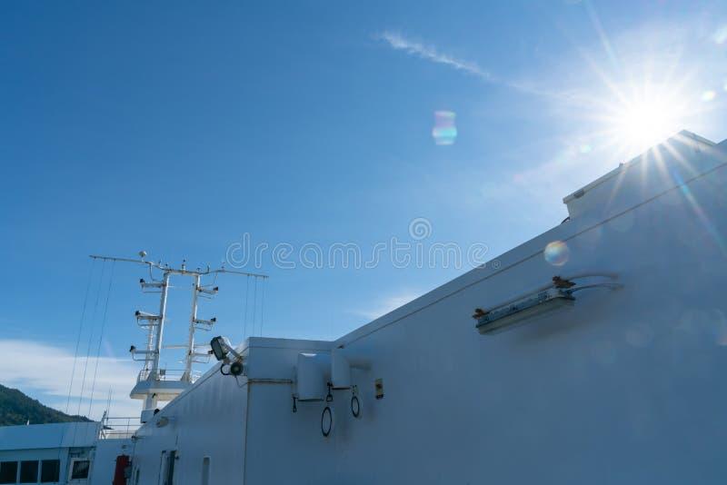 Fusée de lentille du soleil éclatant au-dessus de la superstructure du bateau contre le ciel bleu images libres de droits