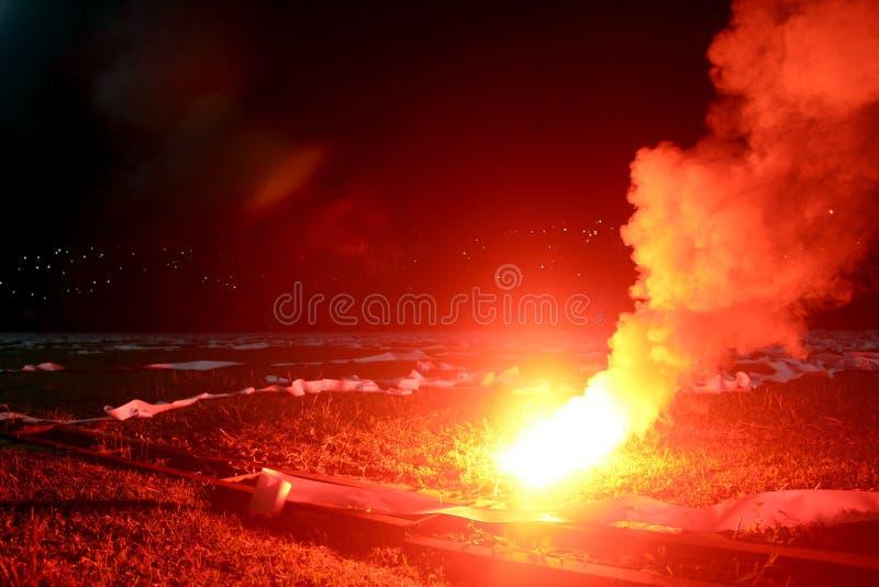 Fusée rouge brûlante, flamme, voyou du football les passionés du football ont allumé les lumières et les bombes fumigènes sur le  images stock