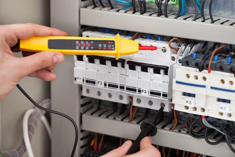 Fusebox d'esame dell'elettricista con il tester di tensione immagine stock libera da diritti