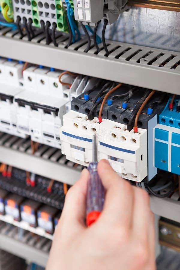 Fusebox de exame do eletricista com chave de fenda imagens de stock
