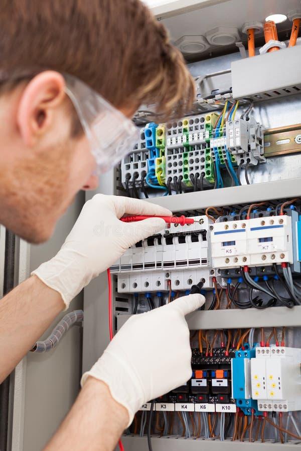 Fusebox de examen del ingeniero eléctrico con la punta de prueba del multímetro imagen de archivo