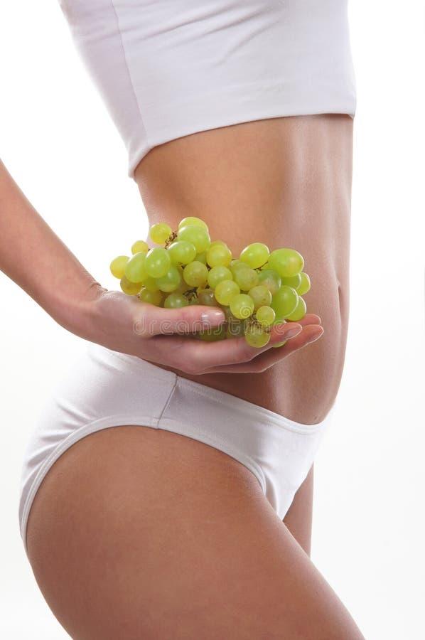 Fuselage sexy des raisins d'une exploitation de jeune femme photos stock