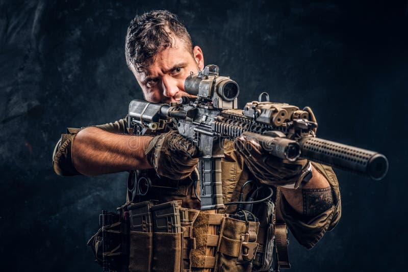 Fusil d'assaut de port de participation d'armure de soldat de forces spéciales et viser l'ennemi image stock