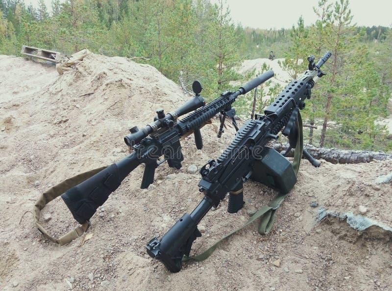Fusil d'assaut et mitrailleuse sur le fond des forêts et du sable de pin photo stock