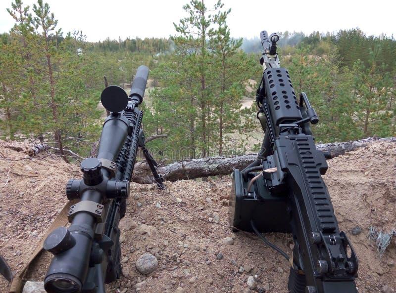 Fusil d'assaut et mitrailleuse sur le fond des forêts et du sable de pin photo libre de droits