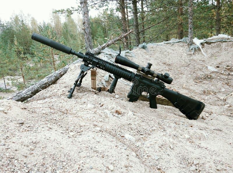 Fusil d'assaut sur le fond des forêts et du sable de pin photographie stock libre de droits
