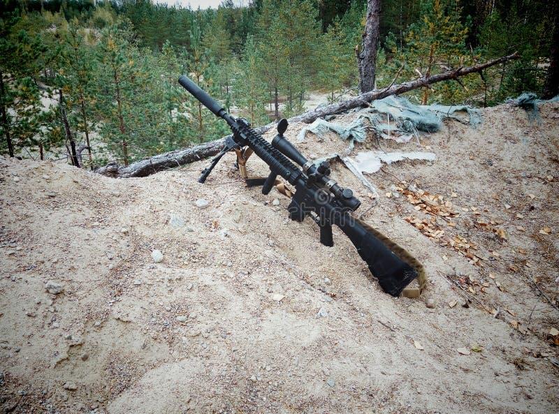 Fusil d'assaut sur le fond des forêts et du sable de pin photo stock