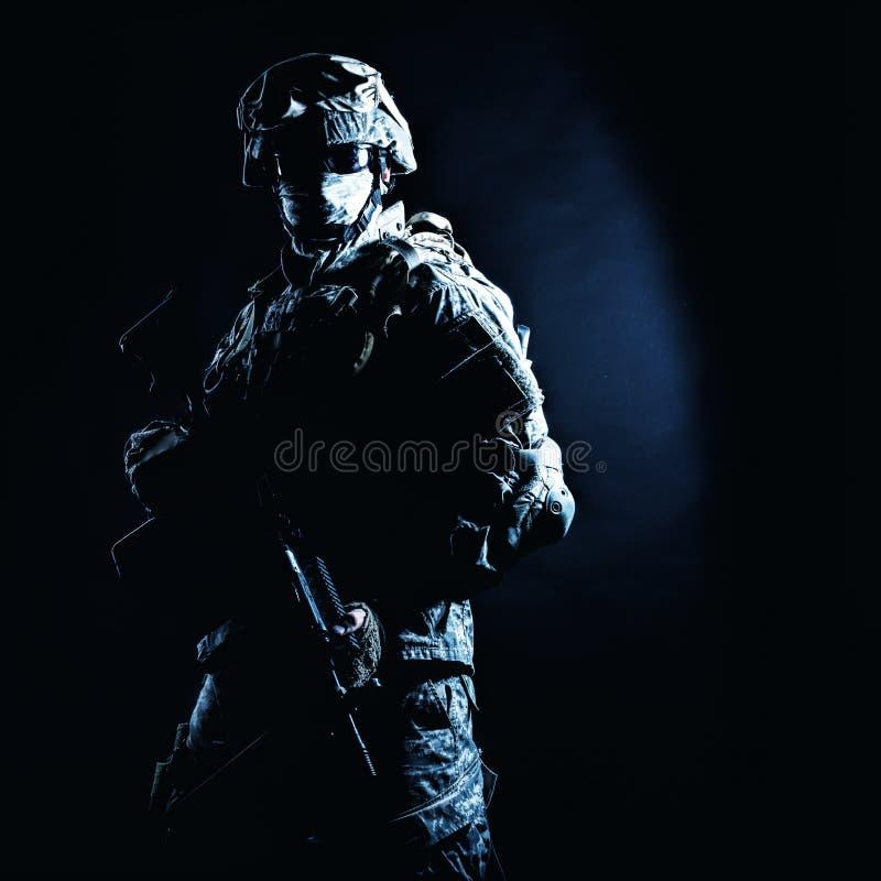Fusilero de la infantería que se coloca con el arma en oscuridad imagen de archivo libre de regalías