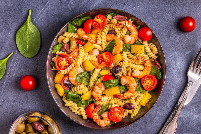 Fusili pasta salad with shrimps. Tomatoes, peppers, spinach, olives, top view stock image