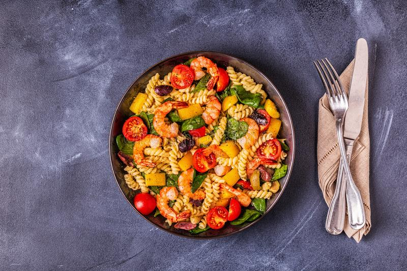 Fusili pasta salad with shrimps. Tomatoes, peppers, spinach, olives, top view stock images