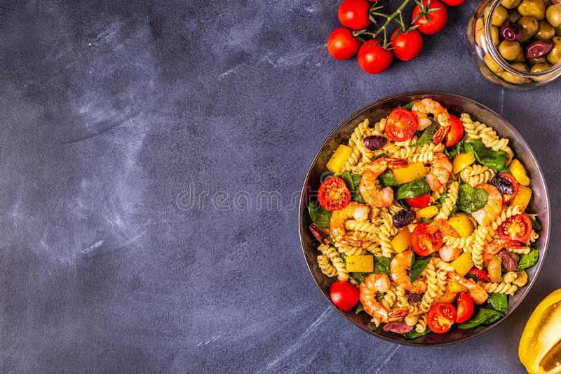 Fusili pasta salad with shrimps. Tomatoes, peppers, spinach, olives, top view royalty free stock images