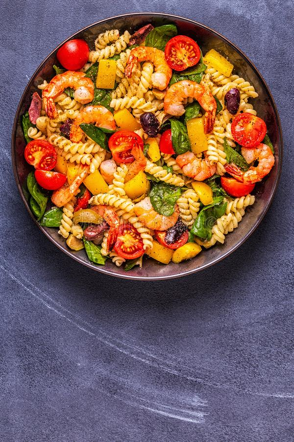 Fusili pasta salad with shrimps. Tomatoes, peppers, spinach, olives, top view royalty free stock image