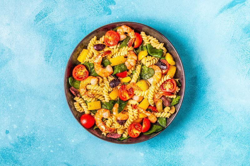 Fusili pasta salad with shrimps. Tomatoes, peppers, spinach, olives, top view stock photos