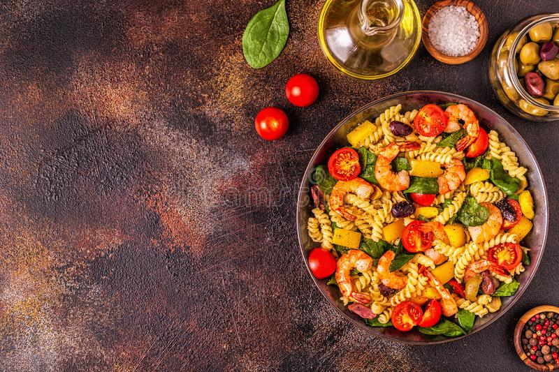 Fusili pasta salad with shrimps. Tomatoes, peppers, spinach, olives, top view royalty free stock photos