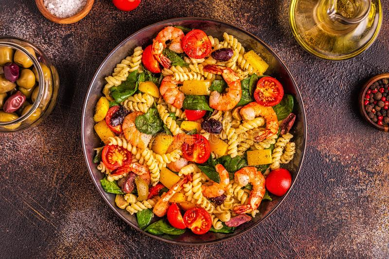 Fusili pasta salad with shrimps. Tomatoes, peppers, spinach, olives, top view royalty free stock photography