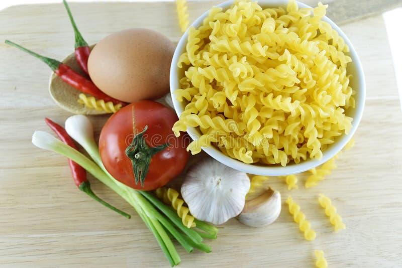 Fusilli、大蒜、辣椒、葱、鸡蛋和蕃茄在木 免版税图库摄影