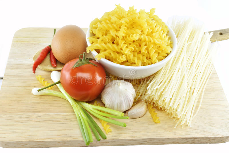 Fusilli、意粉、大蒜、辣椒、葱、鸡蛋和蕃茄在w 免版税库存图片