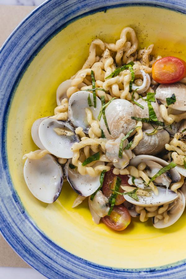 Fusilli Avellinesi pasta with clams and tomato in yellow and blue plate.  royalty free stock photos