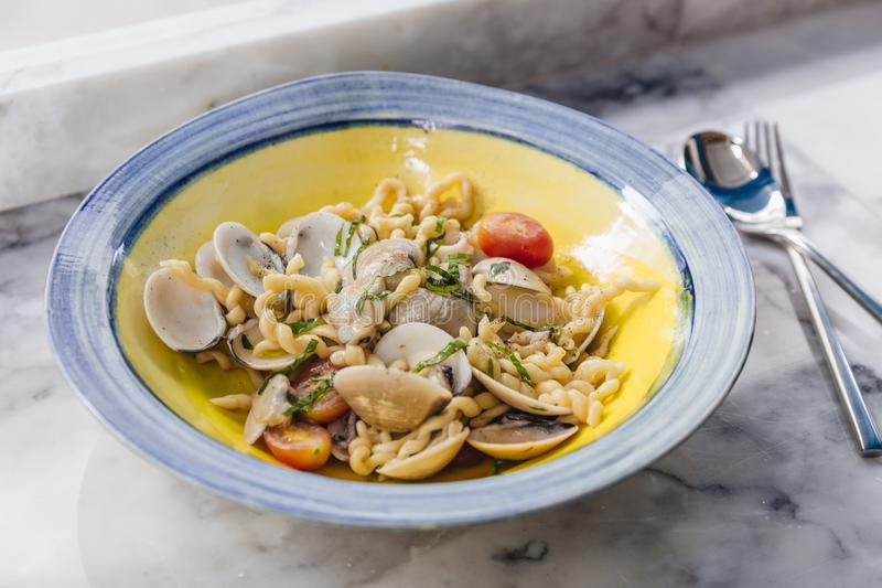 Fusilli Avellinesi pasta with clams and tomato in yellow and blue plate.  royalty free stock photography