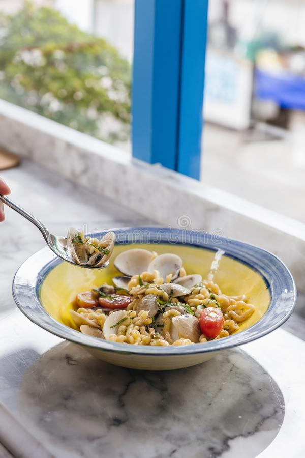 Fusilli Avellinesi pasta with clams and tomato in yellow and blue plate.  stock photography