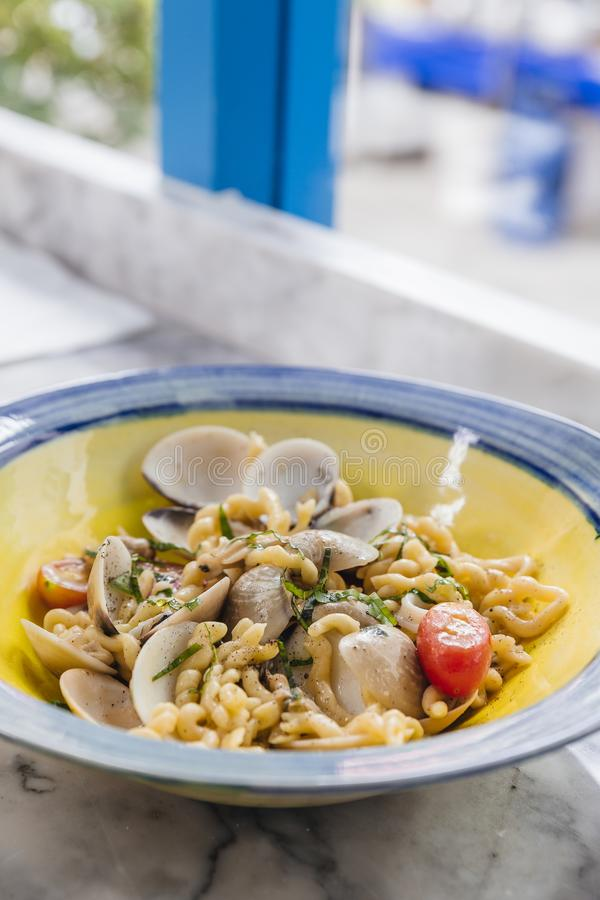 Fusilli Avellinesi pasta with clams and tomato in yellow and blue plate.  stock photo