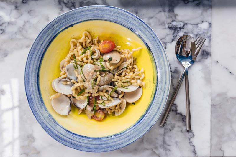 Fusilli Avellinesi pasta with clams and tomato in yellow and blue plate.  stock image