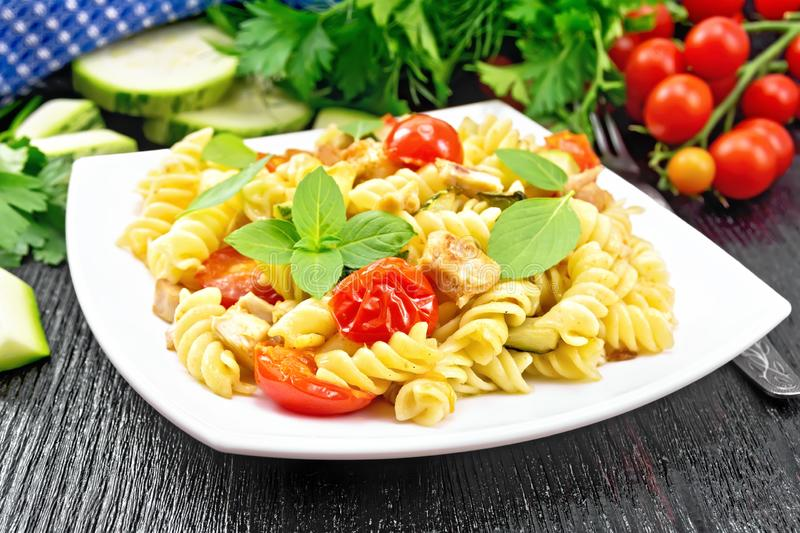Fusilli with chicken and tomatoes in plate on black wooden board stock photos