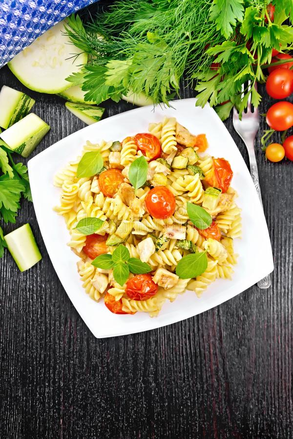 Fusilli with chicken and tomatoes in plate on board top royalty free stock image