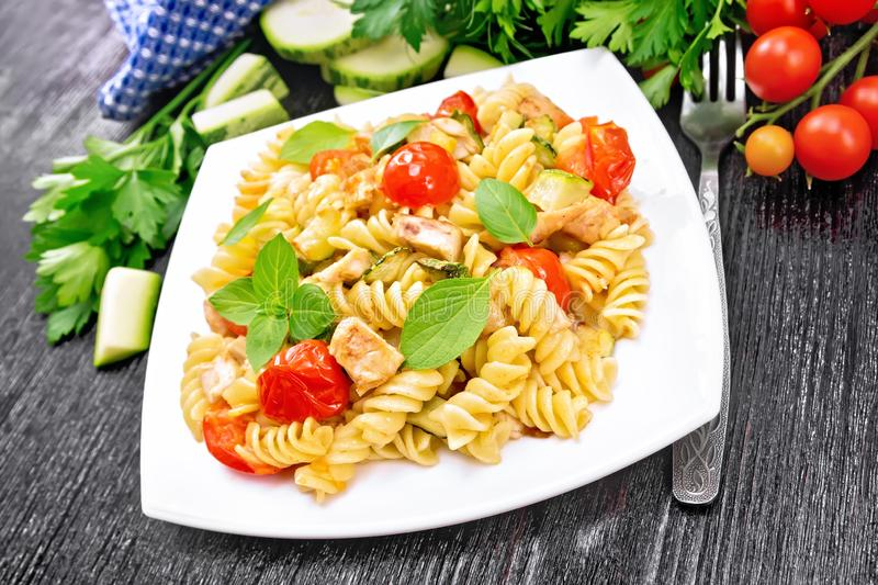 Fusilli with chicken and tomatoes in plate on dark board royalty free stock photo