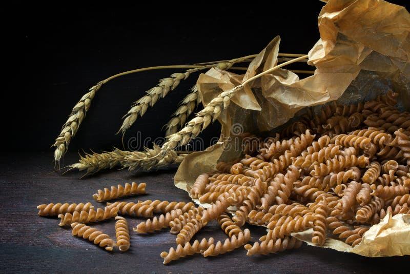 Fusilli complet de pâtes d'écrit dans une oreille de sac de papier et de grain photographie stock