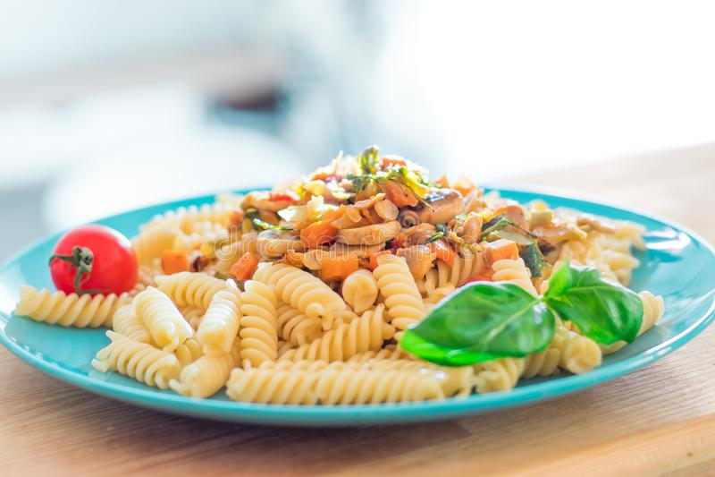 Fusilli cucinato della pasta con i funghi e le verdure fritti sul piatto del turchese fotografia stock libera da diritti