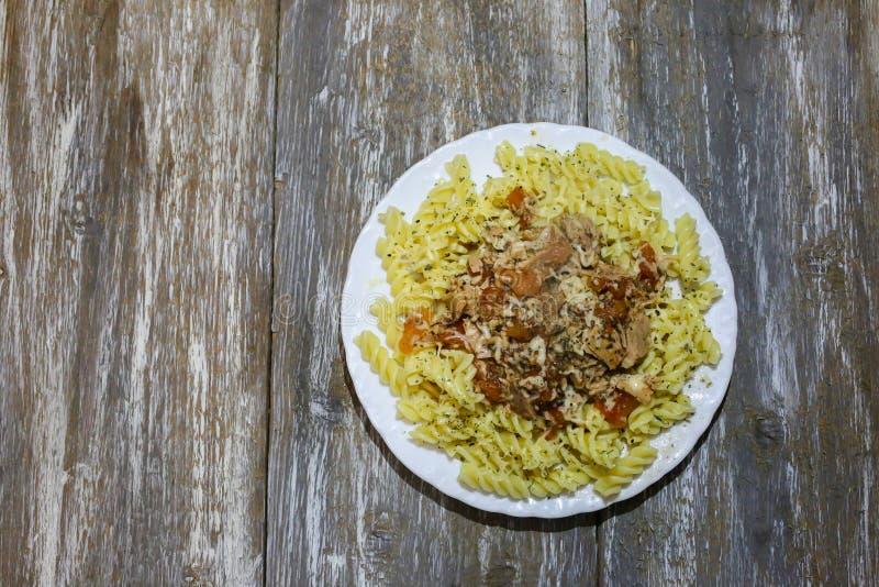 Fusilli med tonfisk och ost på träbakgrunden Hemlagad pasta med tomaten, ost och örter Basilika, oreganon och peppar royaltyfria foton
