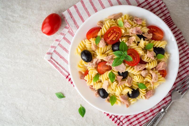 Fusilli-Nudelsalat mit Thunfisch, Tomaten, schwarzen Oliven und Basilikum auf grauem Steinhintergrund stockfotografie