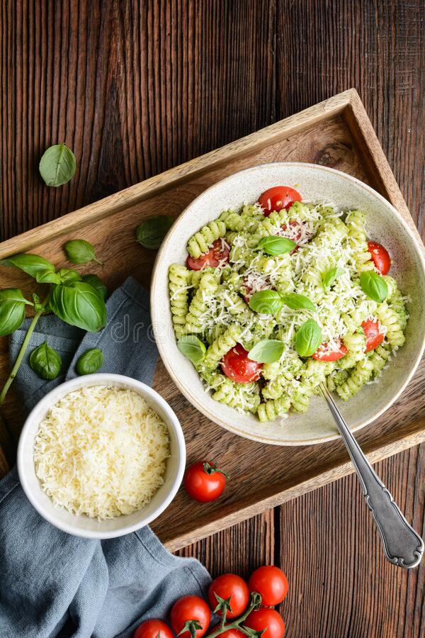 Fusilli pasta with basil pesto sauce and cherry tomatoes, sprinkled with shredded cheese stock images