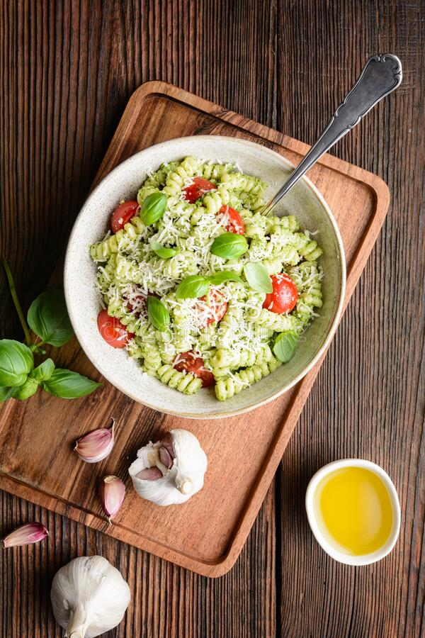 Fusilli pasta with basil pesto sauce and cherry tomatoes, sprinkled with shredded cheese stock photo