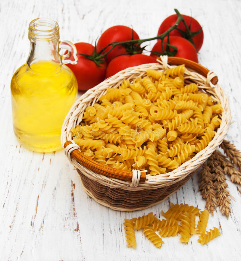Fusilli pasta. Basket with fusilli pasta on a old wooden background royalty free stock photography