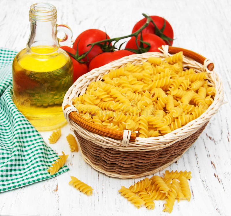 Fusilli pasta. Basket with fusilli pasta on a old wooden background stock photography