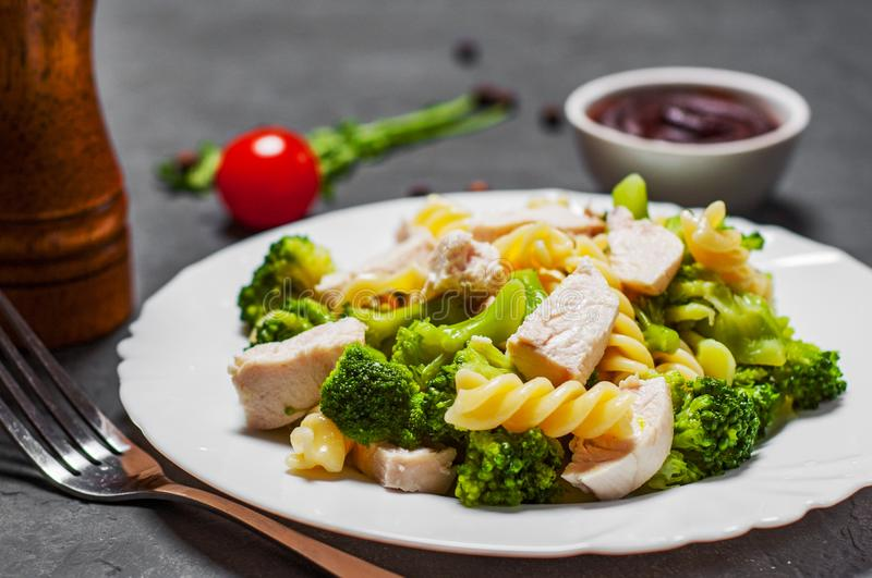 Fusilli pasta with chicken breast and broccoli salad in white plate. On Dark grey black slate background stock images