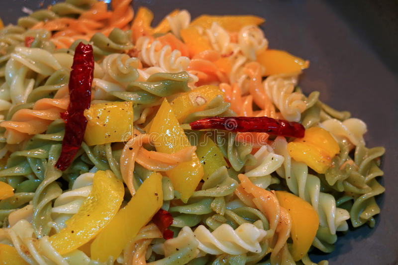 Fusilli pasta with garlic, dried red chili, yellow pepper and olive oil being cooked in a pan. Italian Food stock photo