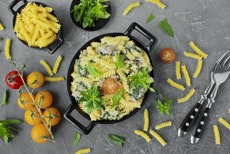 Fusilli pasta med spenat, körsbär, bacon i svart disk arkivbild