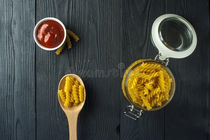 Fusilli pasta och en kopp av tomatsås royaltyfri foto