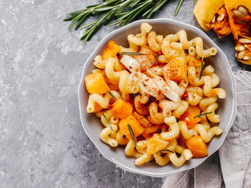 Fusilli pasta with pumpkin, rosemary and brie. Cheese. Idea recipe pasta. Vegetarian food. Homemade pasta dish in gray bowl over gray concrete background. Copy stock image