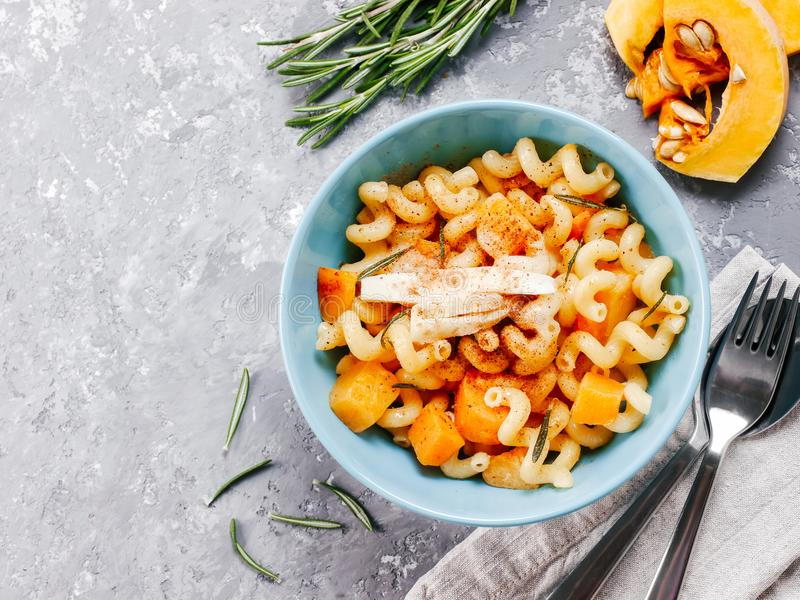 Fusilli pasta with pumpkin, rosemary and brie. Cheese. Idea recipe pasta. Vegetarian food. Homemade pasta dish in blue bowl over gray concrete background. Copy royalty free stock images