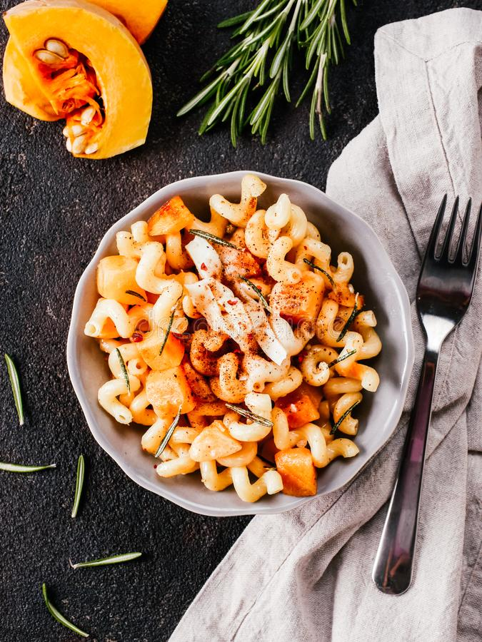 Fusilli pasta with pumpkin, rosemary and brie. Cheese. Idea recipe pasta. Vegetarian food. Homemade pasta dish in gray bowl over black concrete background. Copy stock images