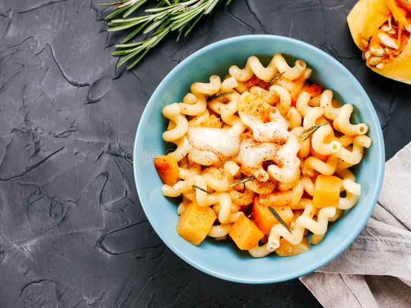Fusilli pasta with pumpkin, rosemary and brie. Cheese. Idea recipe pasta. Vegetarian food. Homemade pasta dish in blue bowl over black concrete background. Copy stock image