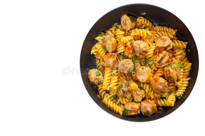 Fusilli pasta with sausage and vegetables in a frying pan. top view. isolated. On white royalty free stock photos