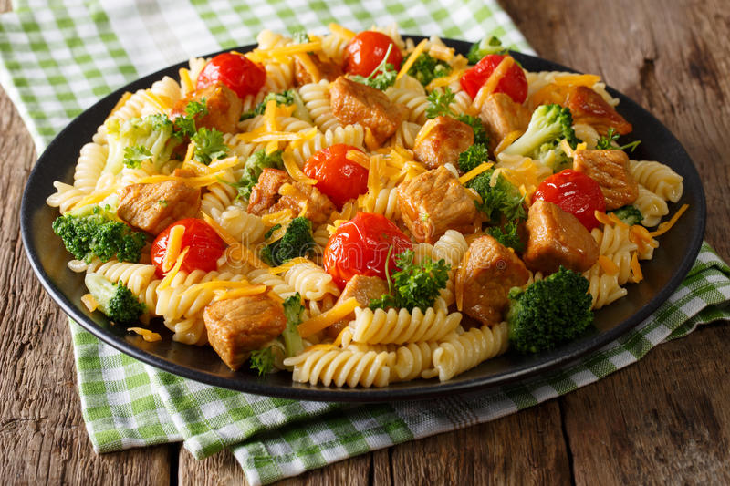 Fusilli pasta with spicy pork, broccoli, tomatoes and cheese che. Ddar close-up on a plate. horizontal royalty free stock image
