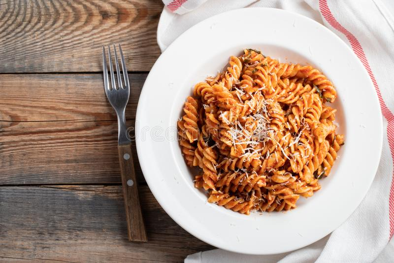 Fusilli pasta with tomato sauce, garlic, Basil and Parmesan cheese on an old wooden table. Top view with copy space. Flat lay royalty free stock image